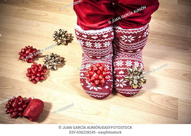 Red knitted boots with fur full of ribbons over wooden floor. Christmas staff concept