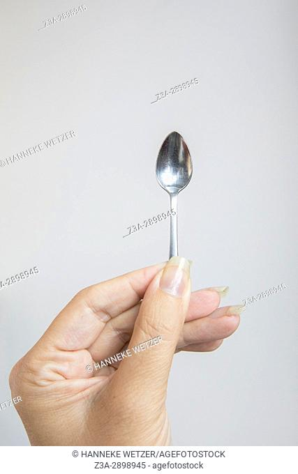 Hand holding a small spoon