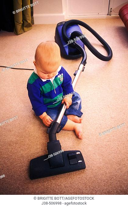 14 month old twin boy playing with hoover