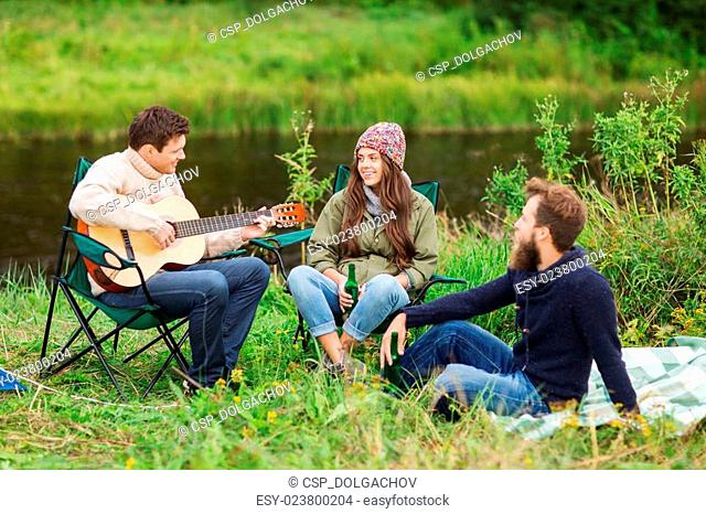 group of tourists playing guitar in camping
