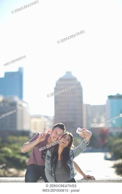 Happy young couple taking a selfie with smartphone