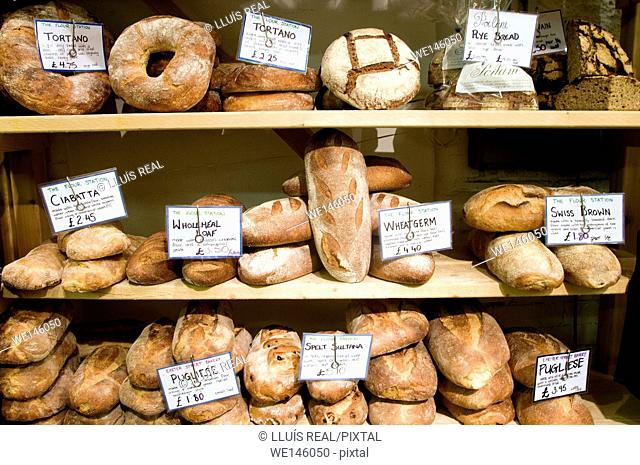 A bakery shelves with different types of bread for sale. Pugliese, Tortano, Rye Bread, Swiss Brown, Wheat Germ, Whole Meal Loaf, Ciabatta, Spelt Sultanas