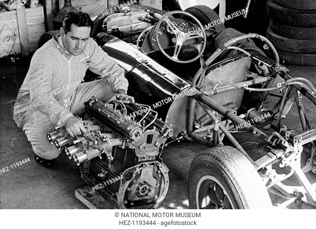 Jack Brabham inspecting the engine of a car. He won three World Championships, twice for Cooper, and the third time at the wheel of a car bearing his own name