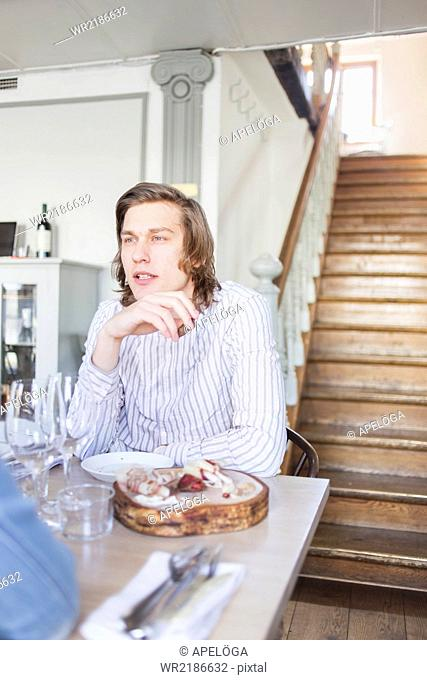 Young man sitting at restaurant table
