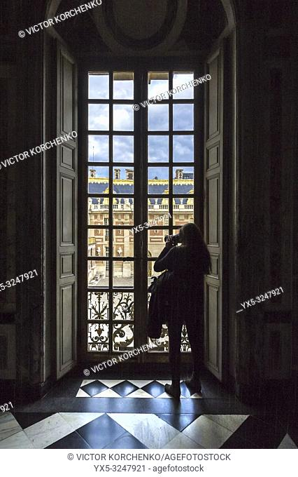 Tourist taking photo through a window at Versailles palace