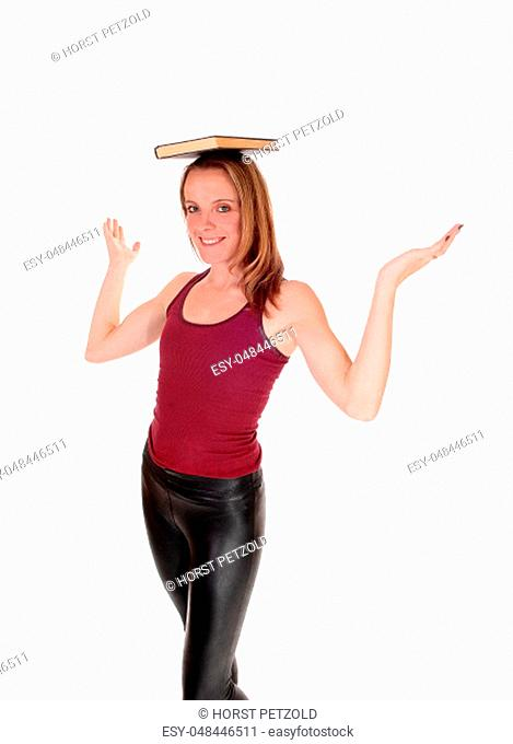 A young smiling woman standing in black leather pants and burgundy.top, balancing a book on her head, isolated for white background