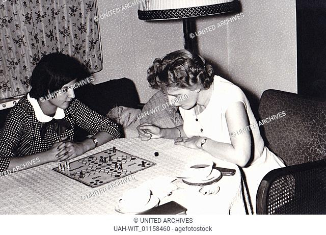 Mutter und Tochter spielen eine Partie Mensch-ärgere-Dich-nicht