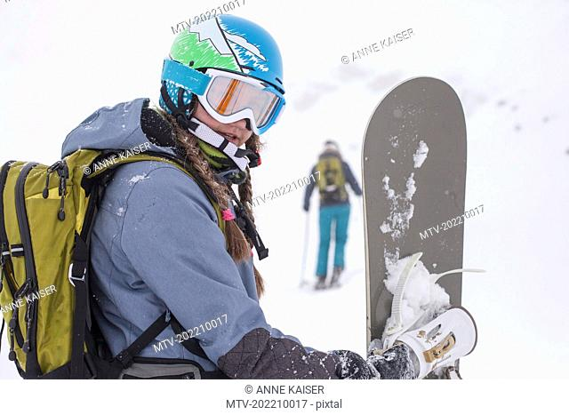 Close-up of girl in ski-wear holding snowboard