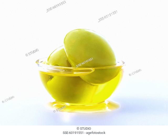 Two green olives with oil in a small bowl