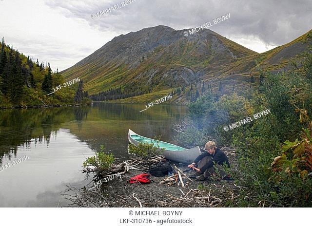 Man sitting at a campfire nwar St. Elias Lake, Kluane National Park and Reserve, Yukon Territory, Canada