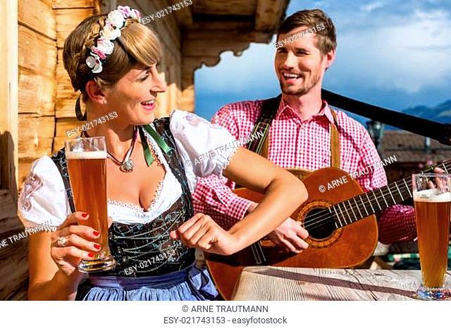 Paar auf Berghütte musiziert mit Gitarre