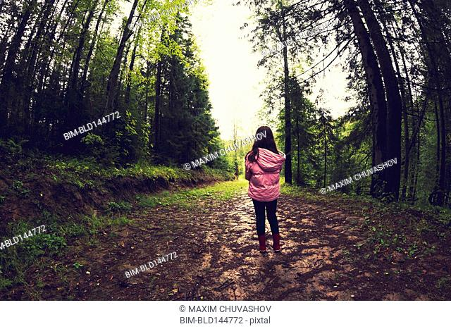 Caucasian girl walking on dirt path in forest