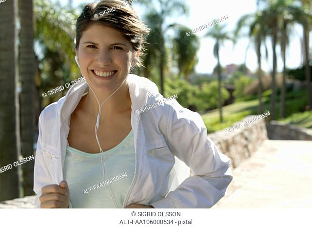 Woman jogging, smiling cheerfully, portrait