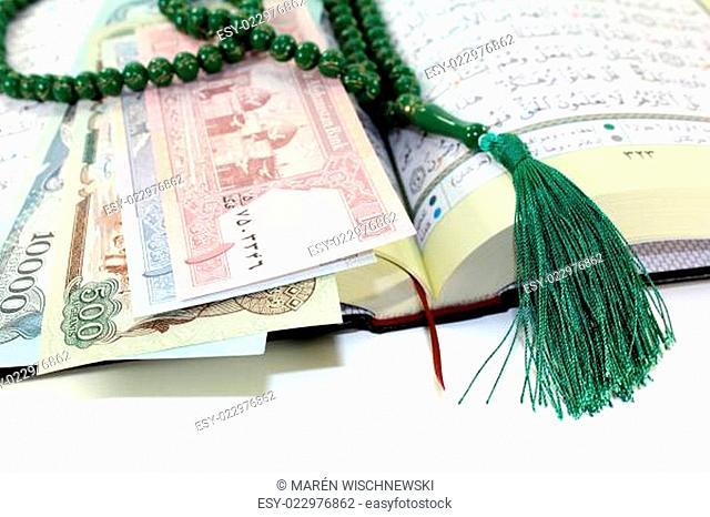 aufgeschlagener Koran mit afghanistanischer Währung