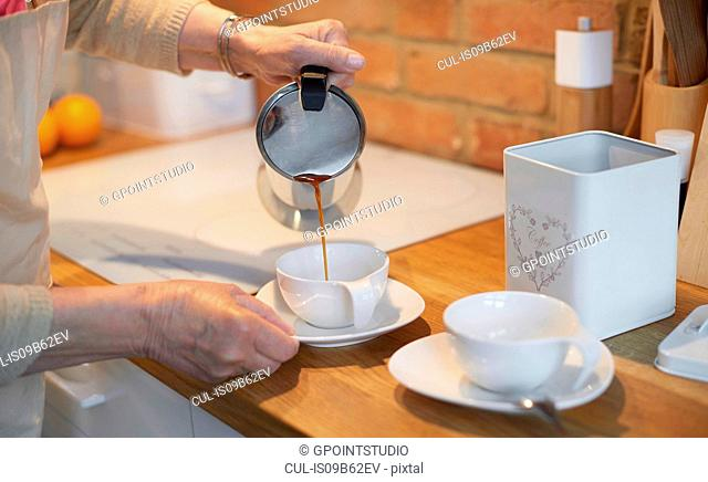 Senior adult woman pouring coffee into cups