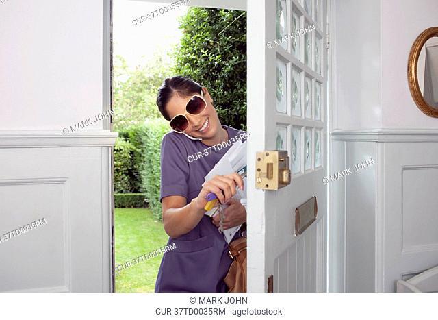Woman on cell phone walking in door