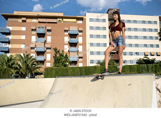 Young pretty woman standing on skate ramp