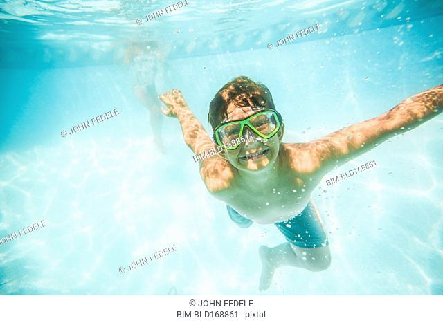 Caucasian boy swimming underwater in swimming pool