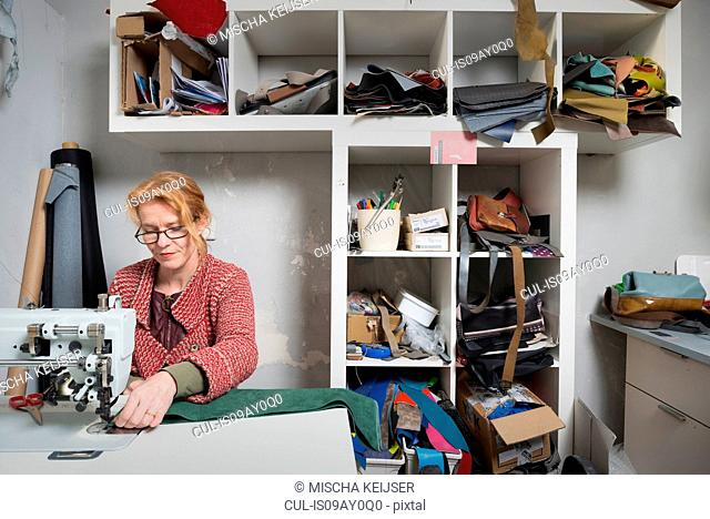 Woman using sewing machine in workshop