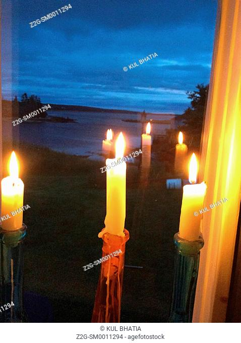 Three candles reflected in a window overlooking the ocean at dusk, Halifax, Canada