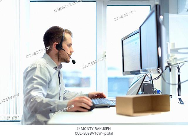 Worker taking customer calls in design department of cardboard box factory
