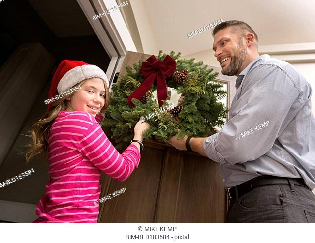 Caucasian father and daughter hanging Christmas wreath