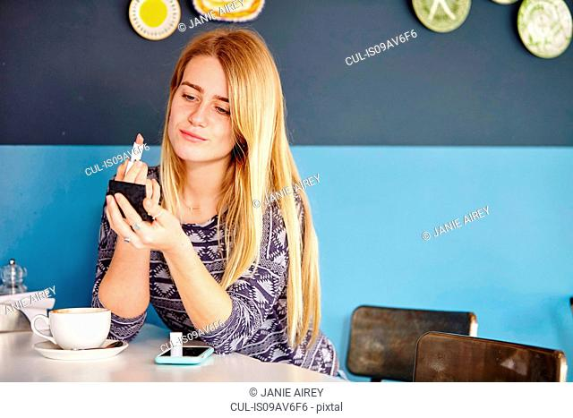 Young woman alone in cafe applying lipstick