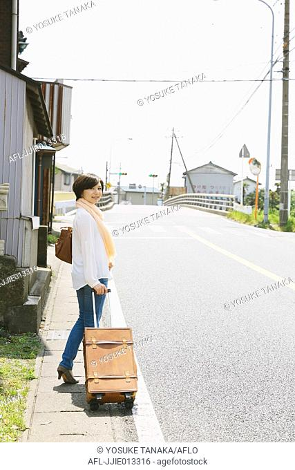 Young Japanese woman walking with suitcase