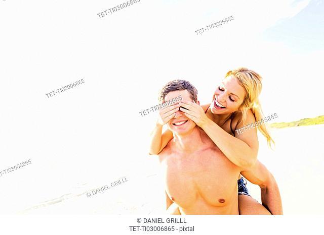 Girlfriend riding piggyback on beach, closing boyfriend's eyes with palms