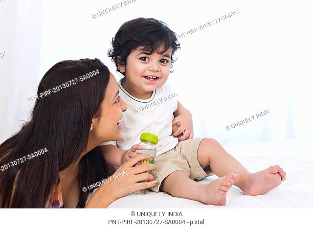 Smiling woman playing with her son