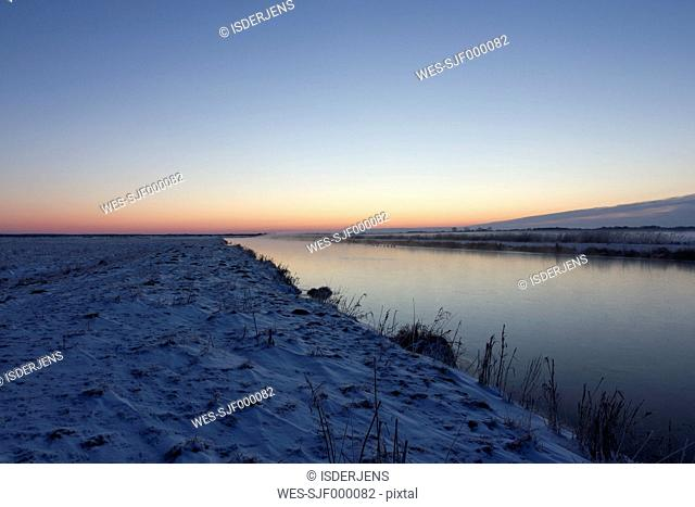 Germany, Lower Saxony, snow covered winter landscape by sunset