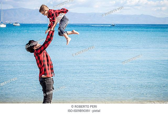 Father and son on beach, father lifting son in air