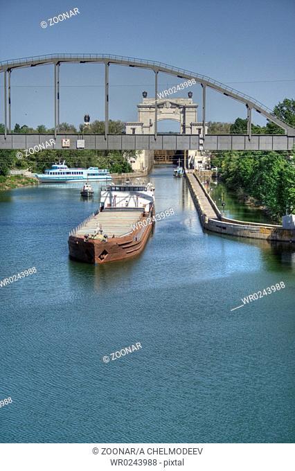 Barge on the Volga-Don canal and railway bridge