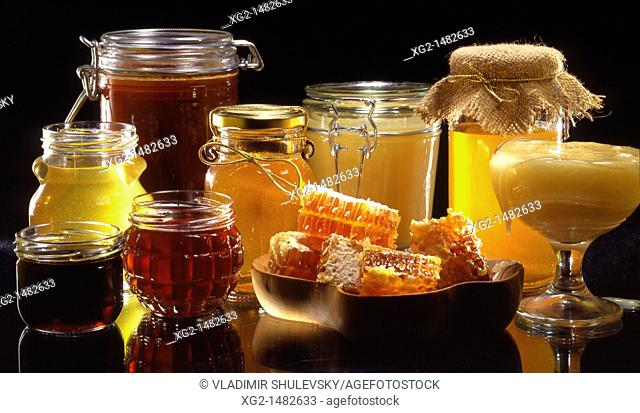 Various types of honey and honeycombs on black background