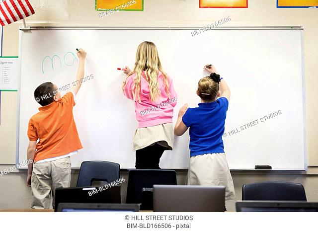 Students writing on whiteboard in classroom