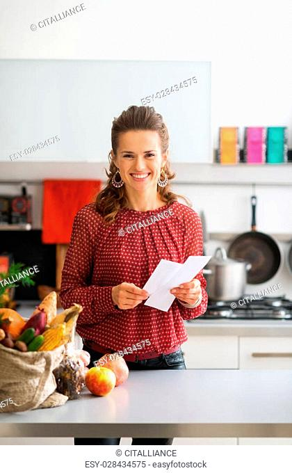An elegant woman is looking up from her shopping lists, smiling happily. On the kitchen counter, a burlap sac holds a variety of fresh autumn fruits and...