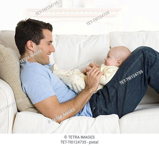 Father smiling at baby on sofa
