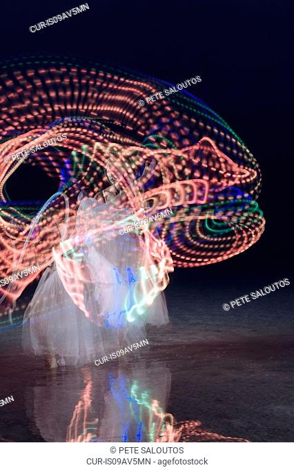 Woman dancing and swirling illuminated multi-coloured hoop at night