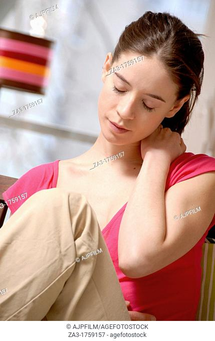 Young woman holding her painful or stiff neck