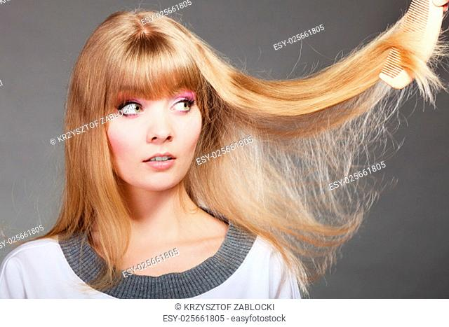 haircare. blonde woman with her dry damaged hair frustrated face expression gray background