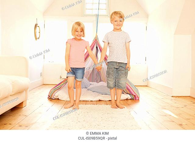 Portrait of boy and girl holding hands in front of bedroom tent
