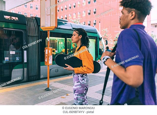 Brother and sister at tram stop, Milan, Italy