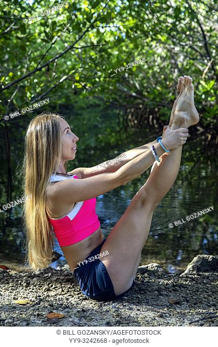 Young woman doing a yoga pose (Modified Boat Pose - Navasana) in a natural setting - Fort Lauderdale, Florida, USA
