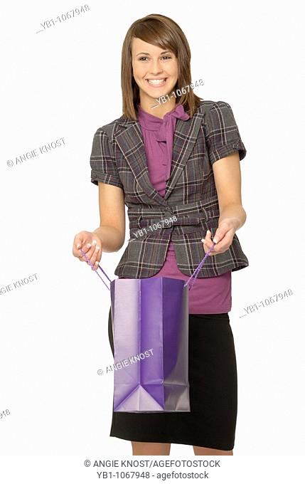 Young adult / teenage girl looking happy while opening a shopping bag