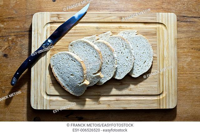 White bread and knife on a chopping board