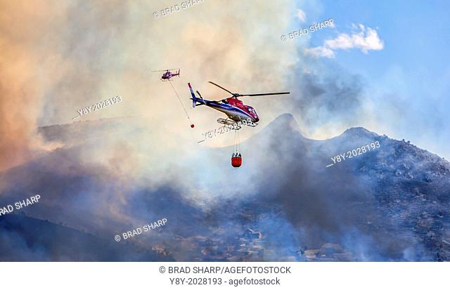 Two helicopters hauling water buckets to fight fire, South Jordan, Utah, USA