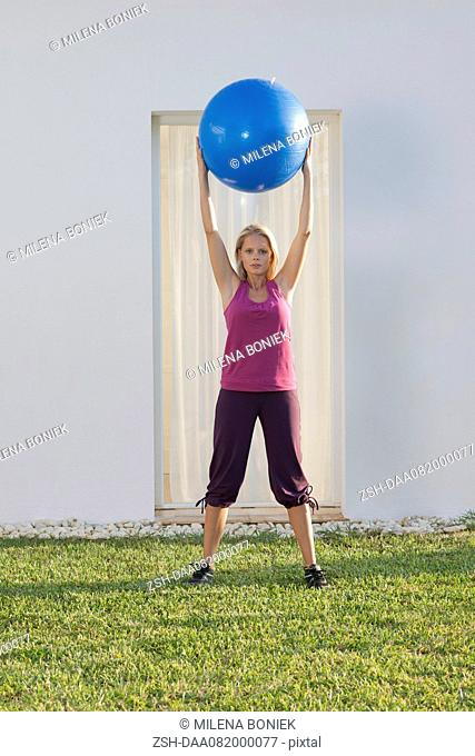Young woman holding up fitness ball above head