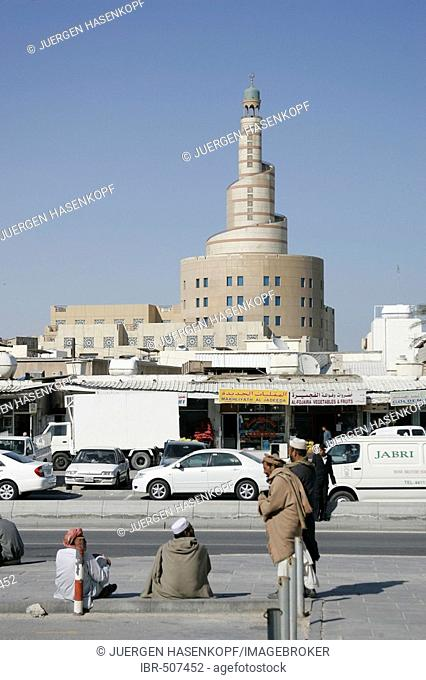 Qatar, Doha, Construction workers sitting on the pavement in the old part of town, in the background the big tower of the FANAR (Qatar Islamic Cultural Center)...