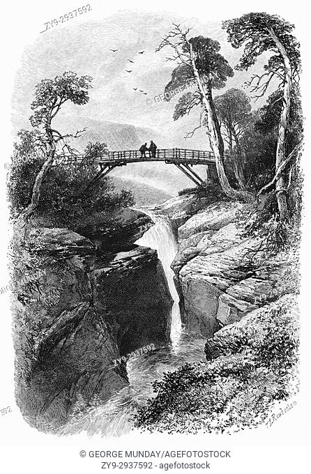 1870: Visitors on the bridge over the Linn O' Dee, a famous beauty spot, much favoured by Queen Victoria. The River Dee runs through a narrow channel and drops...