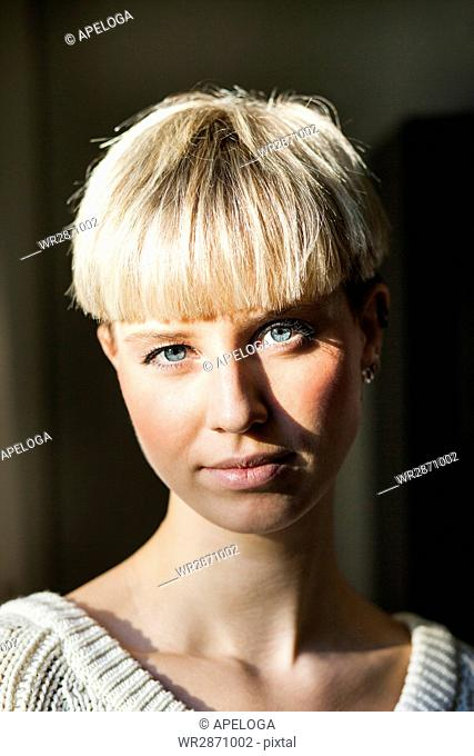Portrait of confident young woman with short blond hair